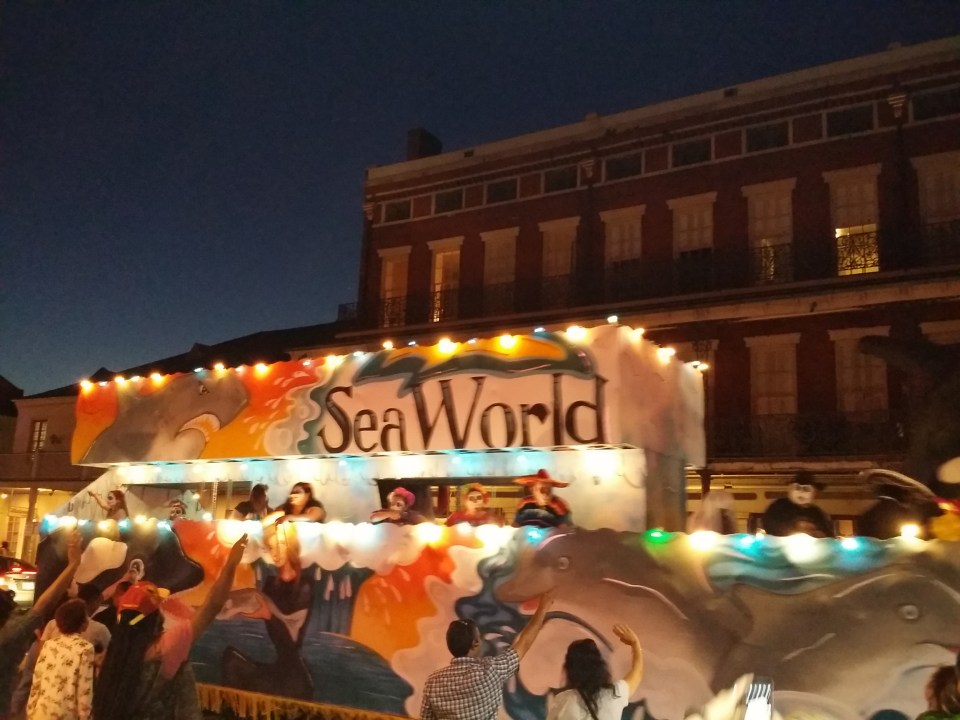 Shows a Seaworld Float parading down the Street outside Jax Brewery in New Orleans