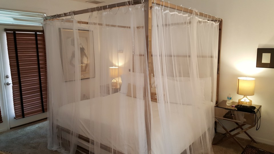 king size bed with Mombassa curtains hung from the posts at the White Orchid Inn