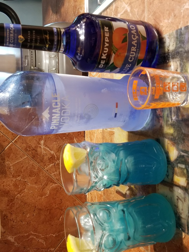 Shows two blue tropical drinks garnished with lemon wedges