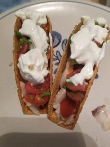 shows 2 fish tacos in hard tortilla shells topped with sour cream