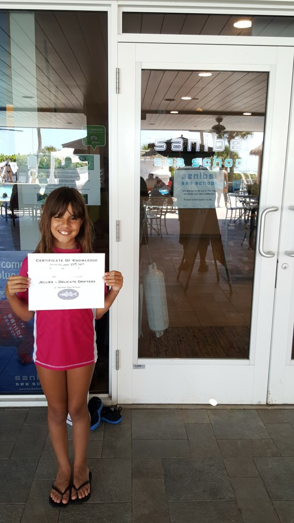 A girl is holding a certificate from Sanibel Sea School