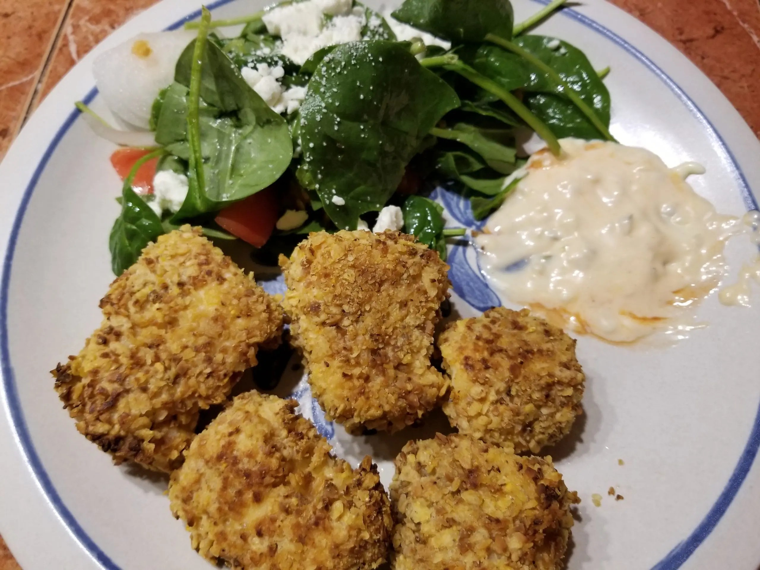 shows coconut fish nuggets with spicy sauce and salad