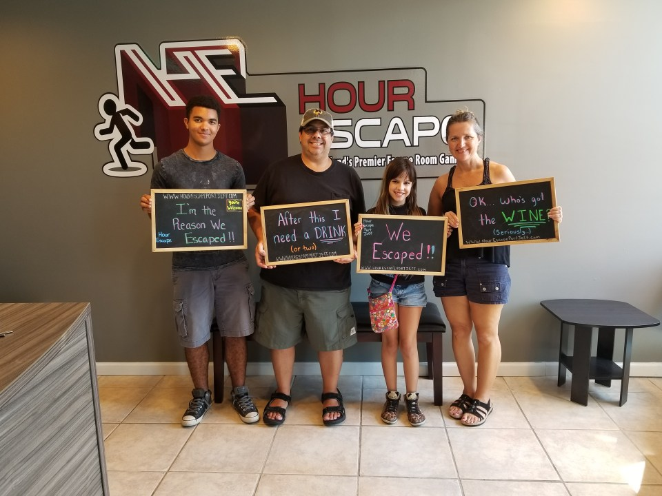 a family holding up signs after completing an escape at Hour Escape in Port Jefferson