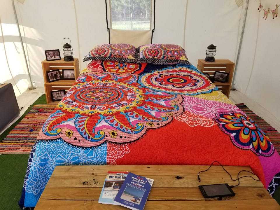 shows a colorful bed with wooden chest and nightstands in a fancy tent