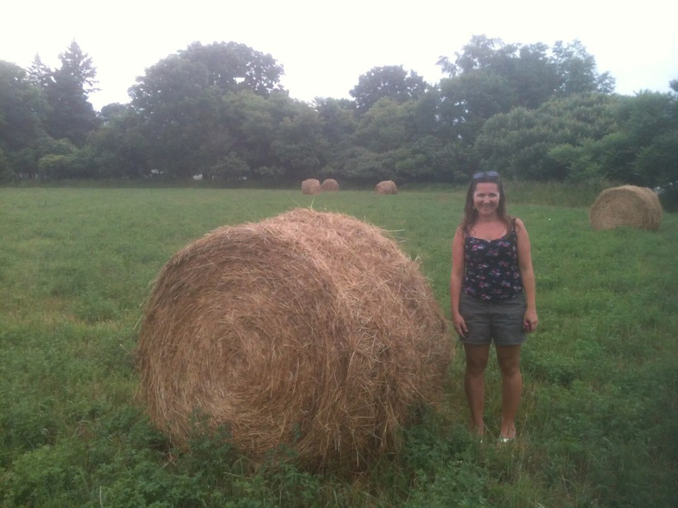 a woman standing next to a haystack in a field in Leicester, NY