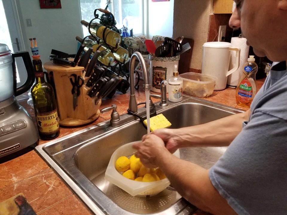shows a person scrubbing lemons to prepare to make limoncello