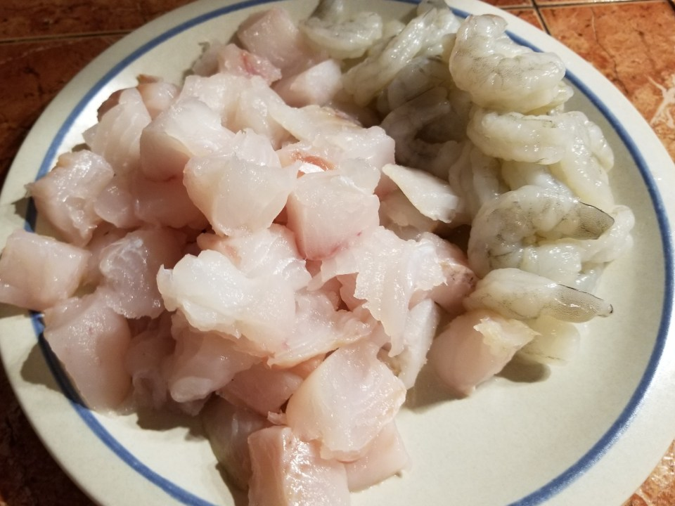 A plate with raw fish and shrimp in preparation for making Boillabaisse for a Valentine Day recipe