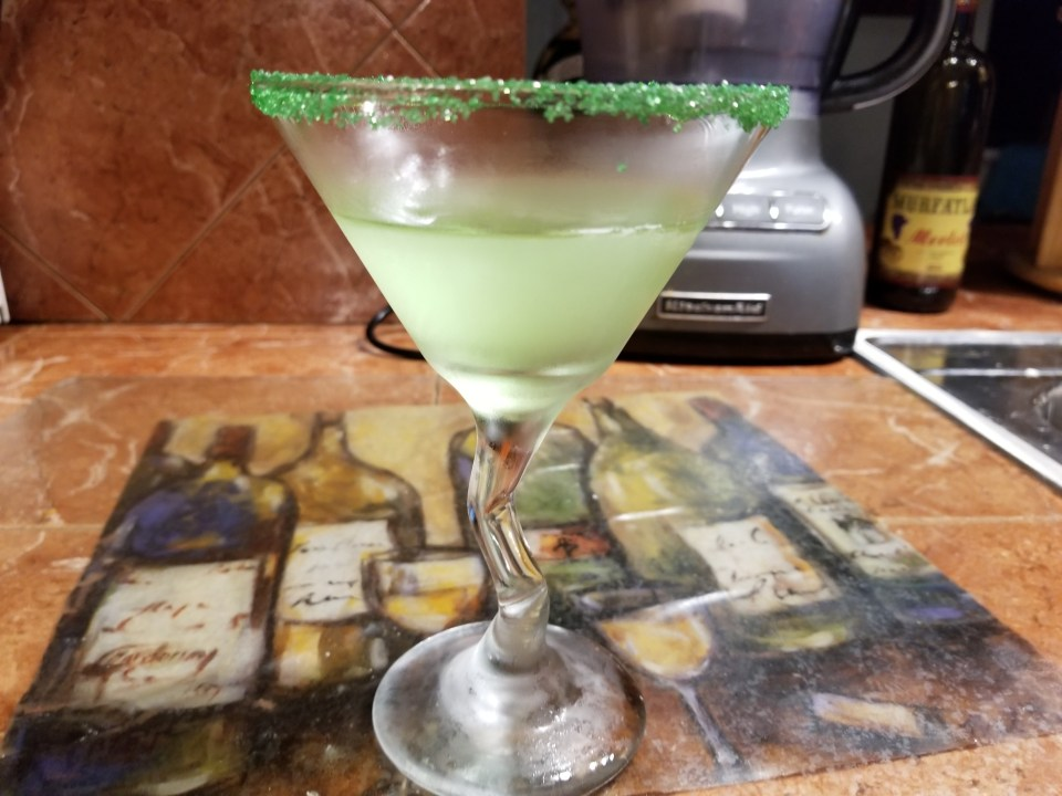 green appletini in a cocktail glass with green sugar rim
