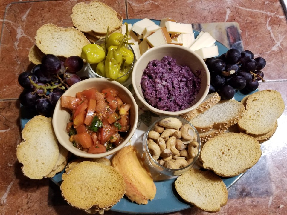 Shows a cheese and meat board with tapenade, Bruschetta, grapes, cheese, peppercini, almonds, a d a toasted baguette