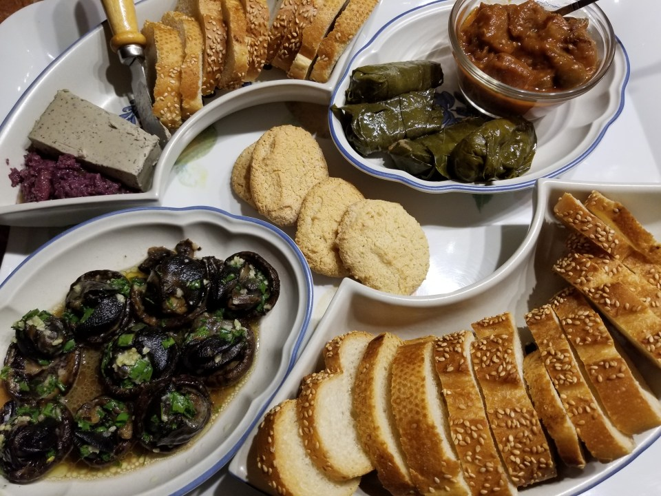 Shows a cheese and meat board with escargot, stuffed grape leaves, food gras, caponata, toasted baguette, and amaretti cookies
