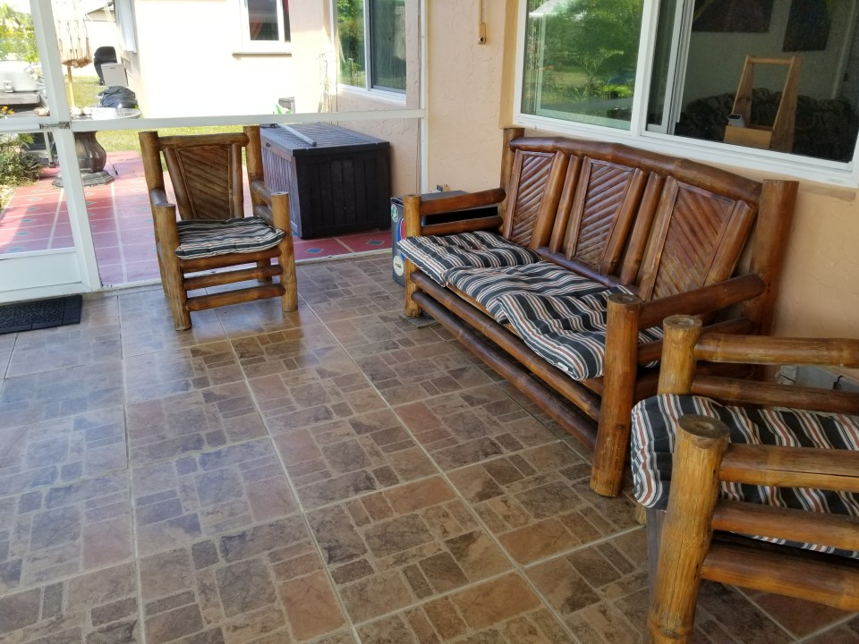 a garden room screened in with tikki love seat and chairs and tiled brick flooring
