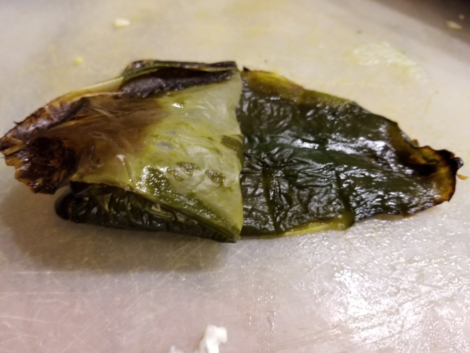 peeling charred skin away from roasted poblano pepper in preparation for poblano best burgers recipe
