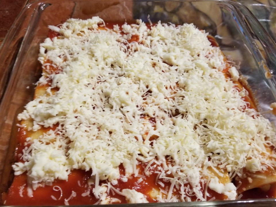 homemade pasta recipes for cannelloni shows pasta in baking pan covered with red sauce and mozzarella cheese
