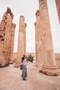 woman standing among tall pillars in Jerash Jordan