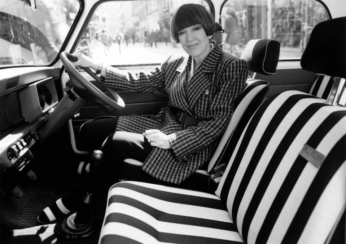 Black and white image of a woman, designer Mary Quant, in the front seat of a vehicle. The seats are decorated with thick striped fabric.