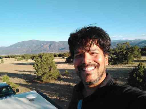 Fulltime RVer taking a selfie on his RV roof with a view of the mountains in Salida, Colorado.