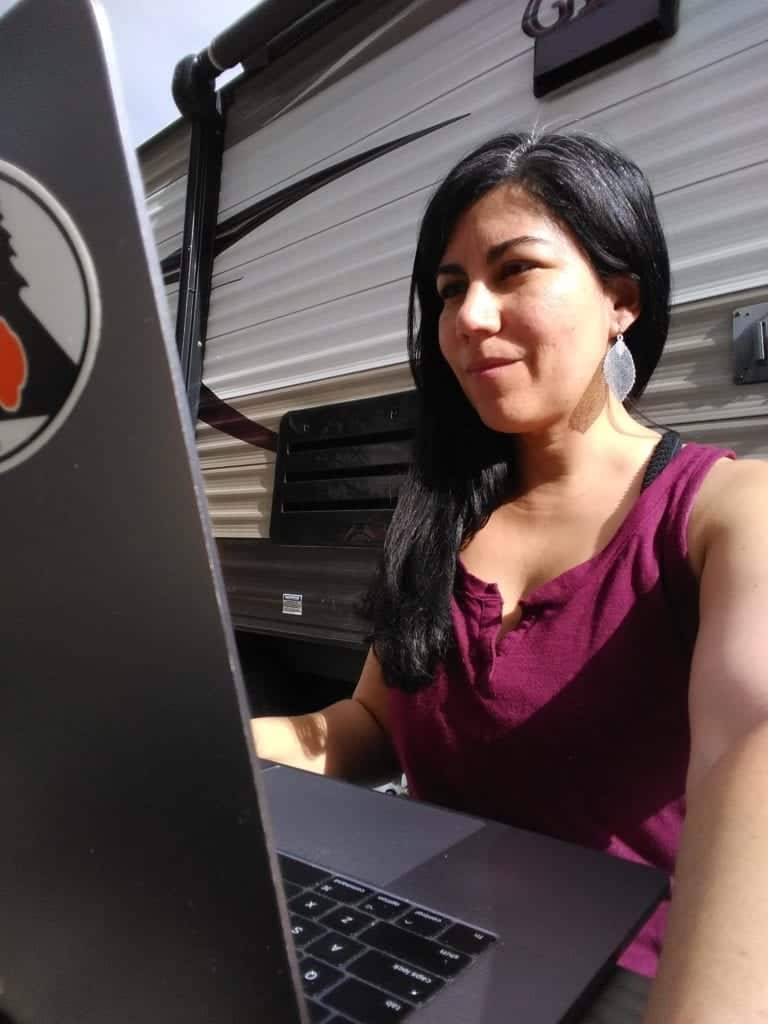 A digital nomad working outside at her campsite using her own unlimited hotspot.