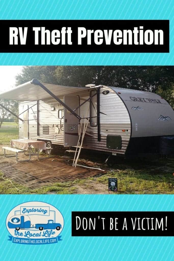 Travel trailer parked on the grass with the awning and front door open.