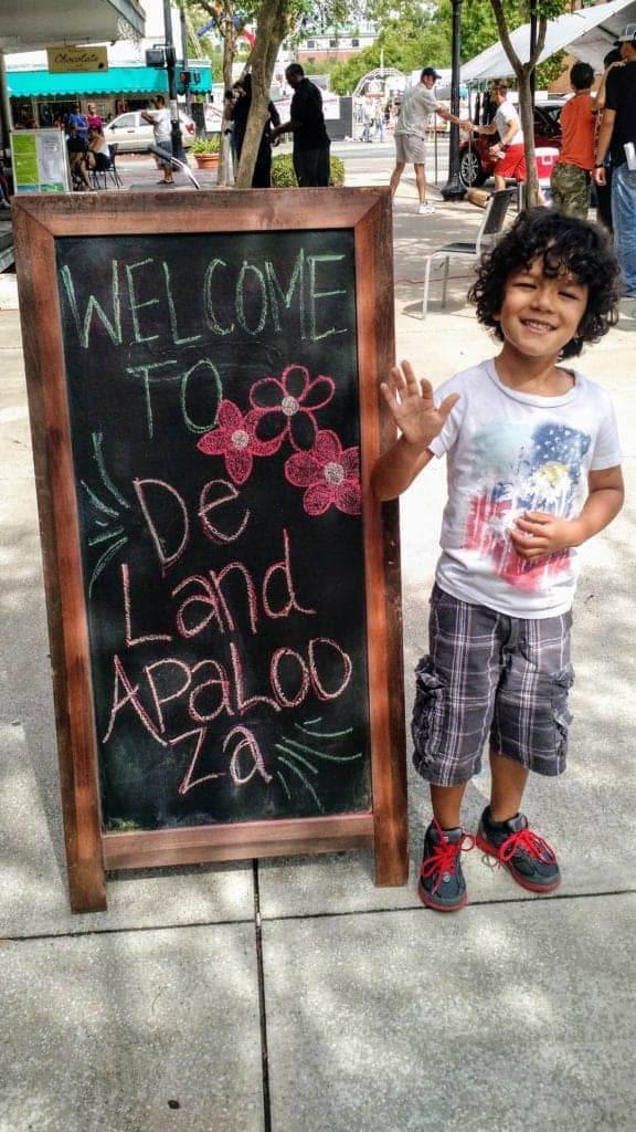 Young boy waving to the camera next to a chalk-drawn sign that reads: Welcome to DeLandapalooza.