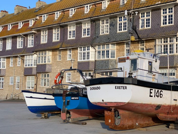 Fishing boats outside a block of flats in West Bay
