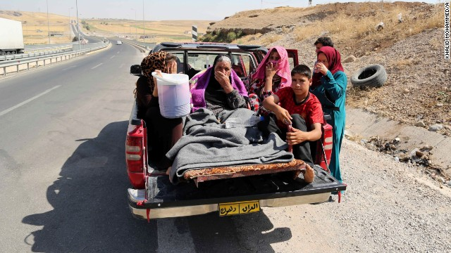 Displaced Iraqis ride on a truck on a mountain road near the Turkish-Iraq border, outside Dahuk on August 9.