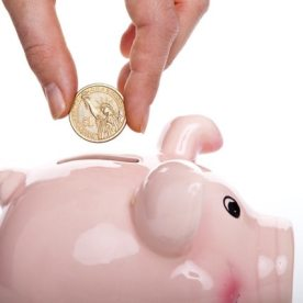 Hand puts coin into piggy bank.