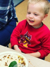 Boy smiling with empty lunch plate.