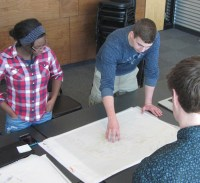 High school students look at design on paper.
