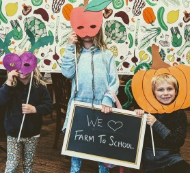 Three students with vegetable masks and We Love Farm to School sign.
