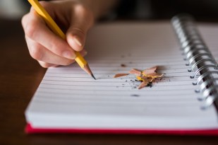 Hand writing on notebook with pencil next to pencil shavings.