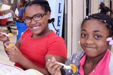 Two girls eat squash.