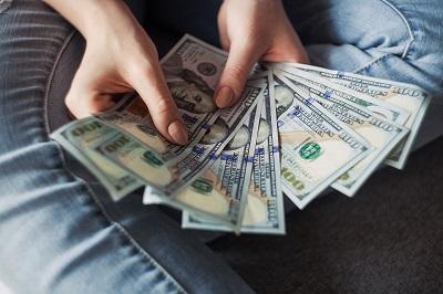 Person holding hundred-dollar bills.