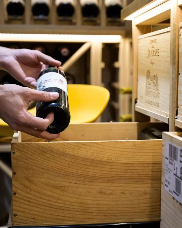 Hands putting wine bottle into wine storage box. Photo by Instagram user @sorrells_wineracks