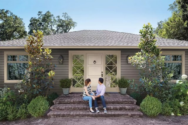 Young couple sitting outside house on porch. Photo by Instagram user @royalbuildingproducts