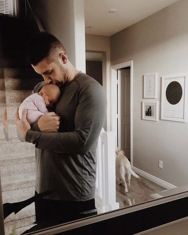 Dad holding newborn baby at home. Photo by Instagram user @littlesleepies