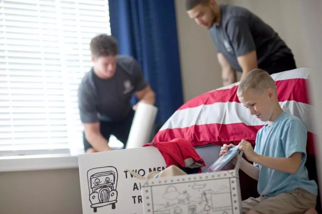 Professional movers helping young boy with his moving boxes. Photo by Instagram user @twomenandatruck