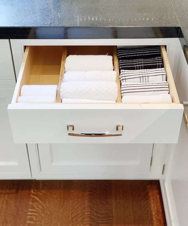 Organized kitchen drawer with folded towels. Photo by Instagram user @neatmethod