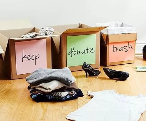 Boxes labeled keep, donate, and trash filled with clothes. Photo by Instagram user @chiropractic_family_wellness