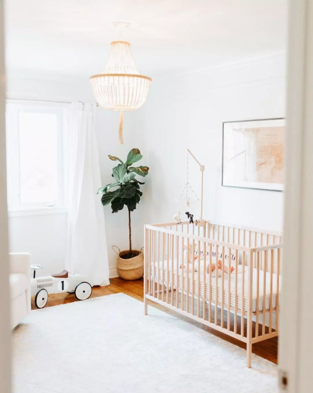 Neutral baby room with chandelier. Photo by Instagram user @laurakelly.co
