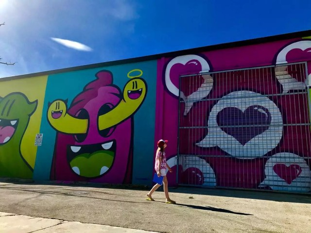 Woman walking in front of colorful mural on side of building Photo by Instagram user @iamsarahgrafferty
