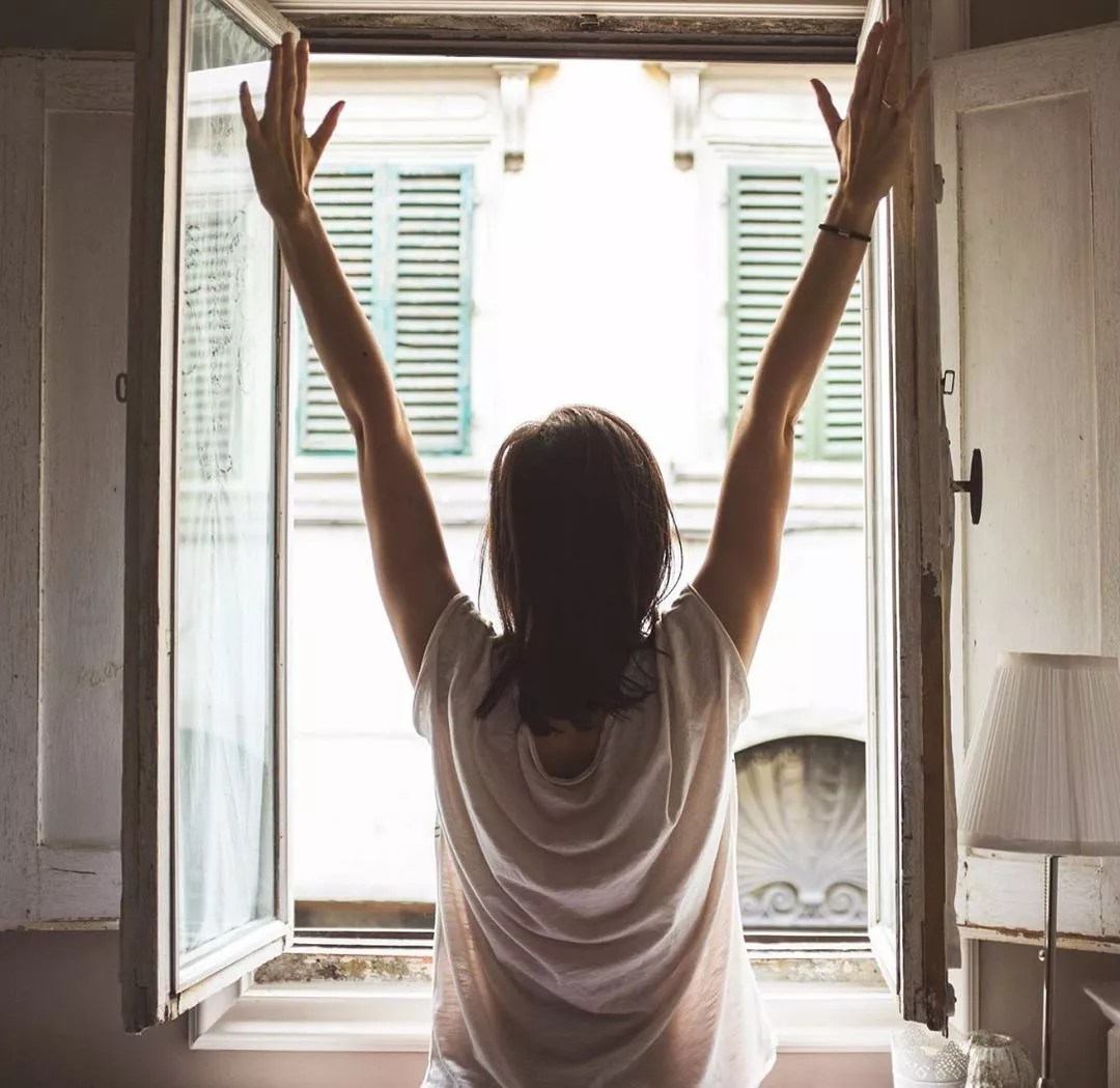 Woman stretching in front of window. Photo by Instagram user @vohanwellness