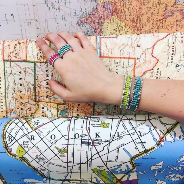 Hand pointing to map wearing colorful bracelets. Photo by Instagram user @samesky