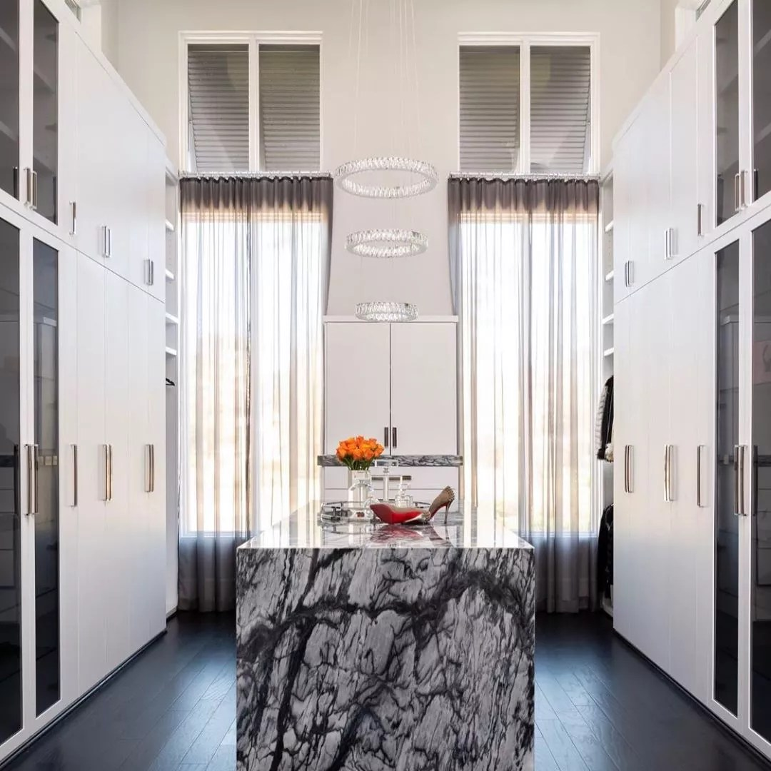 Contemporary closet with marble island. Photo by Instagram user @teripughstudio