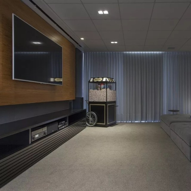 home theater with large flatscreen TV, popcorn machine, and curtains to blackout light photo by Instagram user @veridianaperesarquitetura