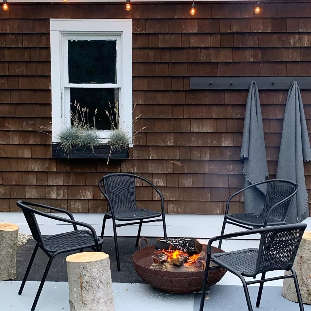 four chairs surrounding a small firepit with logs as side tables for minimalist design photo by Instagram user @most_lovely_things
