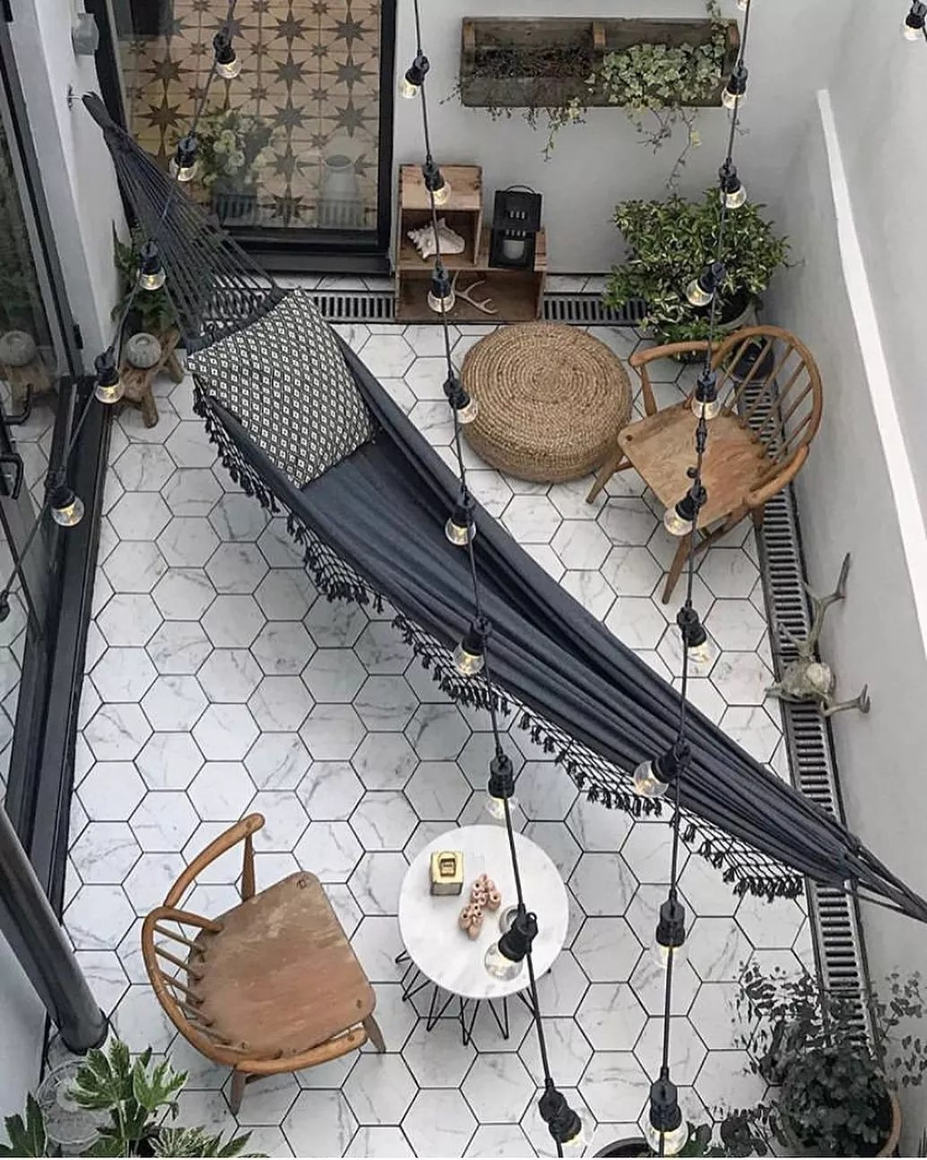 small patio with chairs and a hammock stretched across photo by Instagram user @ravenhawkdesigns