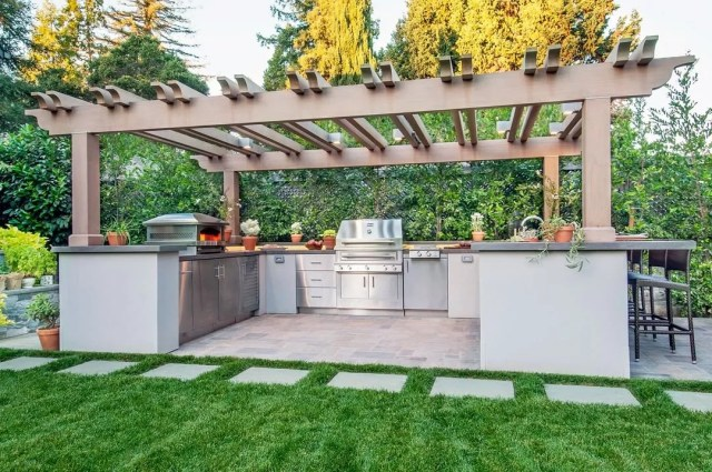 outdoor kitchen built under pergola for shade photo by Instagram user @kalamazoogrills