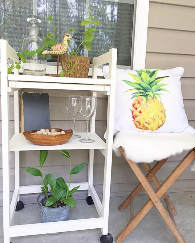 bar cart in outdoor kitchen area with stool next to it with pineapple pillow photo by Instagram user @athomeinthewildwood
