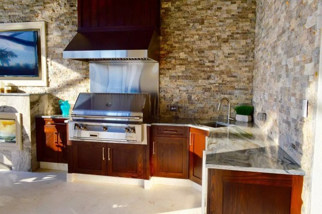 outdoor kitchen with sink and grill that has a hood installed overhead photo by Instagram user @edswflrealtor