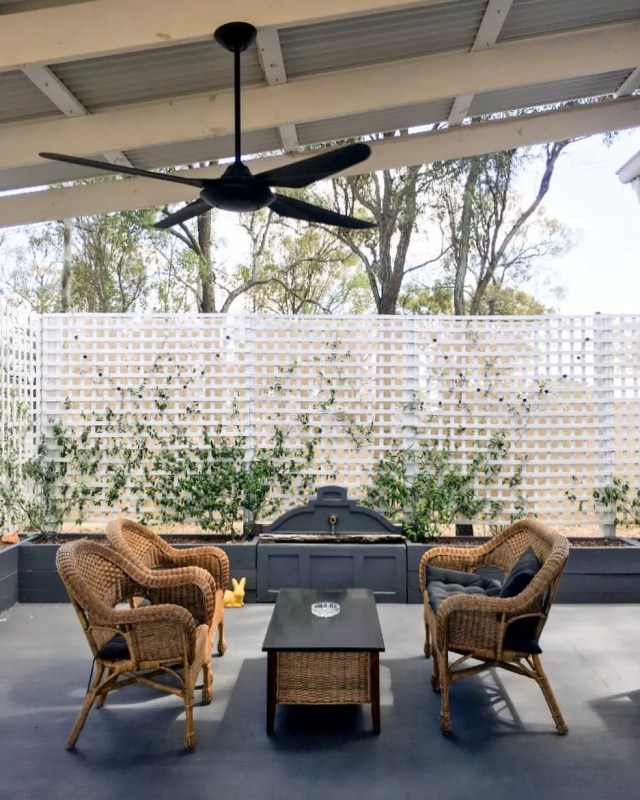 outdoor patio with wicker chairs and black floor with a fan on the ceiling photo by Instagram user @myhuntergatherer